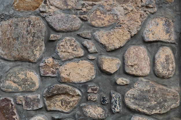 Grey dark stone wall uneven rock surface decorative vintage tile of weathered facade building
