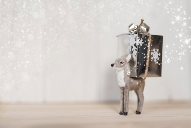 Grey deer carrying a christmas gift with copy space