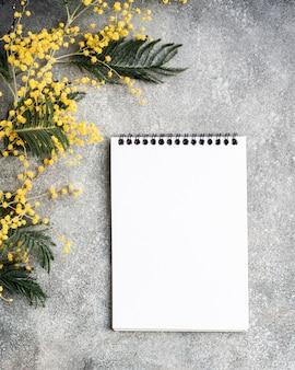 노란색 미모사 꽃 부케와 깨끗한 노트북, 플랫 레이가있는 회색 책상