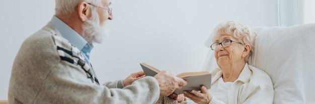 Серый пожилой мужчина вручает книгу старшему другу, лежащему на больничной койке