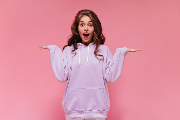 Grey-eyed surprised woman in purple hoodie looks into camera