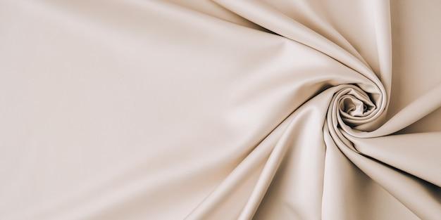 Серая предпосылка картины ткани, дизайн размахивая серой предпосылкой текстуры ткани. шелковая или атласная текстура золотистого цвета шампанского. скопируйте место для текста. текстура фона