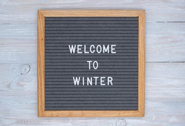 Серая фетровая доска с надписью на английском языке welcome to winter. вид сверху на деревянный стол