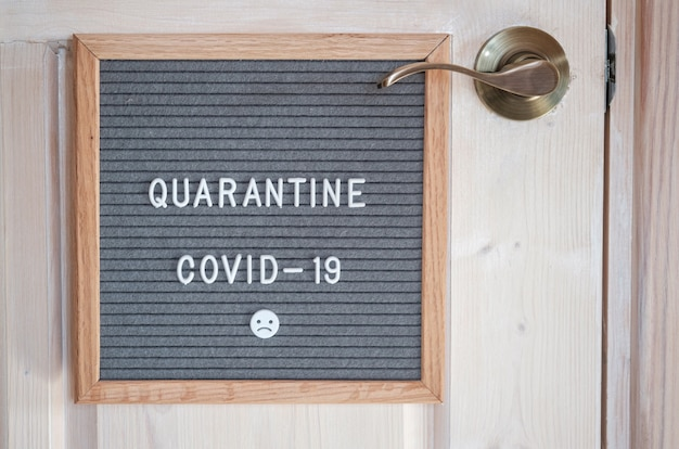 Серая фетровая доска с текстом covid-19 quarantine. концепция карантина во время пандемии коронавируса. призыв не выходить из дома