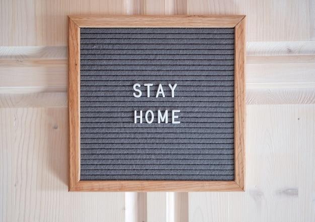 Серая фетровая доска с текстом stay home. концепция карантина во время пандемии коронавируса. призыв не выходить из дома