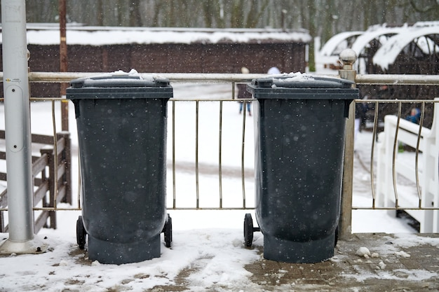 Grey garbage bins on street in winter. public trash containers on side of road