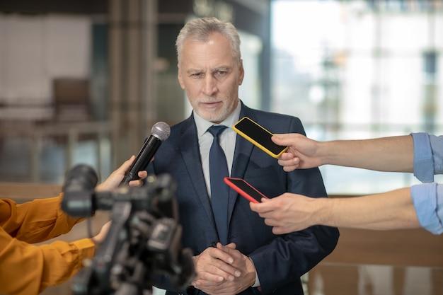 Седовласый бородатый мужчина в элегантном костюме выступает на пресс-конференции