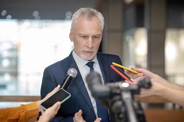 Седовласый бородатый мужчина сосредоточенно смотрит на пресс-конференцию