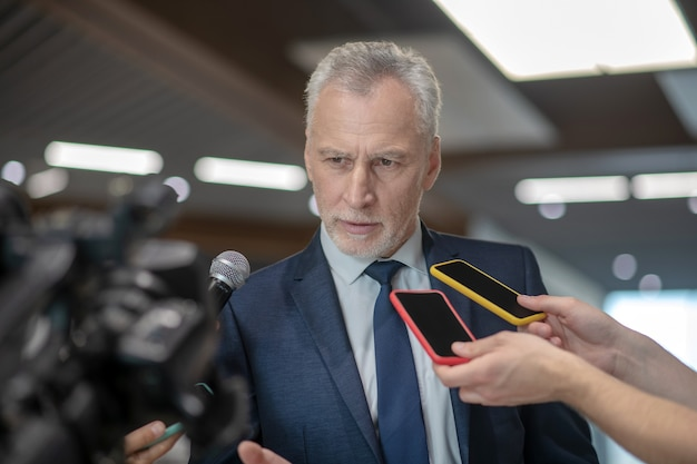 Grey-haired bearded man looking serious while having the press conference