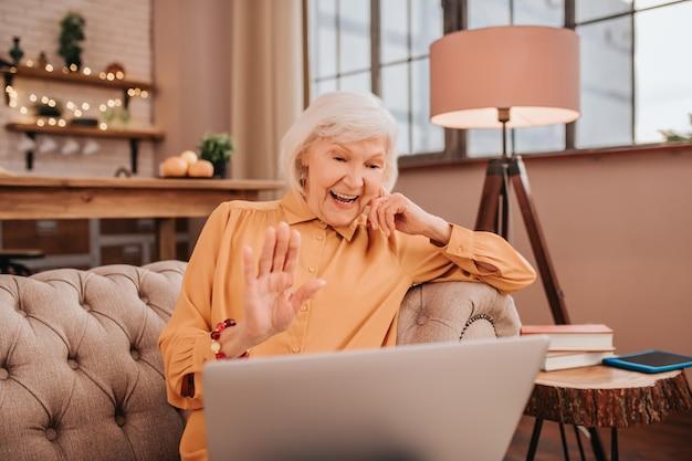 그녀의 친구를 온라인으로 인사하는 오렌지 블라우스에 회색 머리 아름다운 아가씨