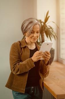 デジタルタブレットを使用してビデオ通話をしている白髪の美しい成熟した女性。ビジネスウーマンのフリーランサーがビデオリンクを介して交渉しています。着色されたビデオ。