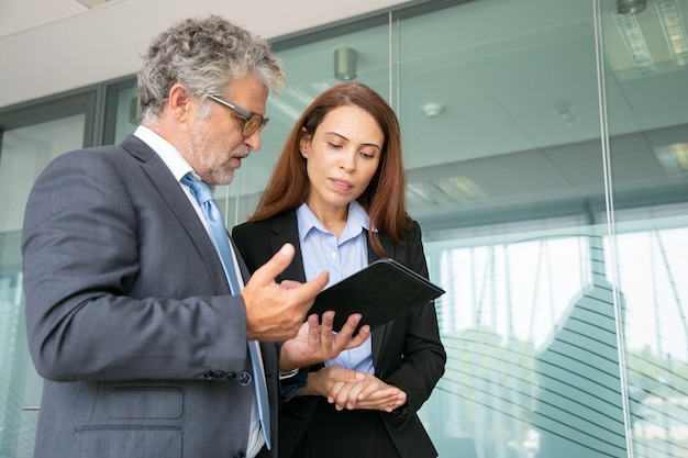 Grey-haired boss discussing with assistant, holding tablet and standing in conference room