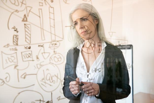 통계 데이터를보고 생각하는 회색 머리 사업가. 마커를 들고 사무실 방에 서 심각한 경험이 풍부한 사려 깊은 여성 관리자. 전략, 비즈니스 및 관리 개념
