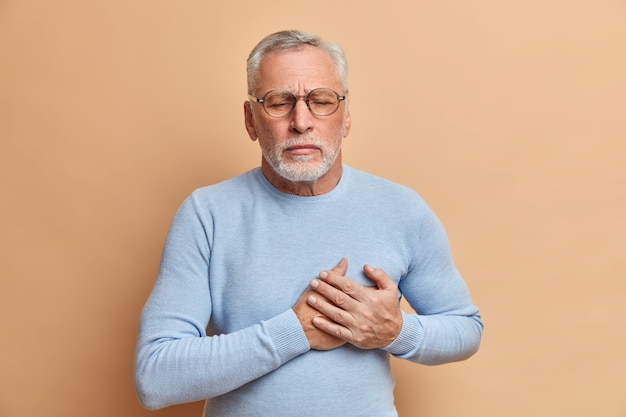 Grey haired displeased bearded old man has sudden painful spasm in chest closes eyes and presses hands to heart poses against beige wall