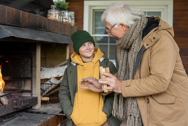 暖かいカジュアルウェアを着た灰色の髪の祖父が、かわいい孫に家のそばのパティオに立っているときに暖炉を燃やす方法を説明しています