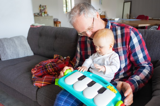 Grey haired grandfather sitting on couch and playing with baby