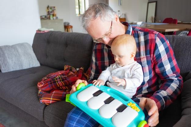 ソファに座って、赤ちゃんと遊ぶ灰色の髪の祖父