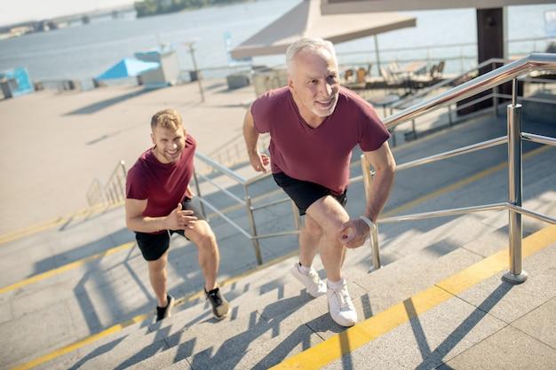 階段を駆け上がる白髪の男性と若い男性
