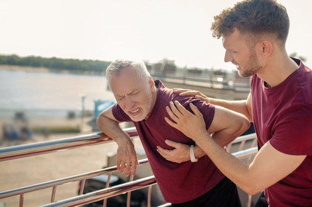 Седовласый мужчина держит руку на груди, молодой мужчина помогает ему