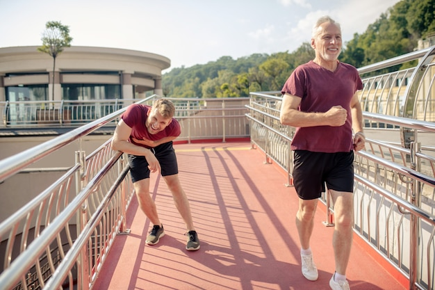 Grey-haired male jogging across bridge, young male holding hand on his chest behind him