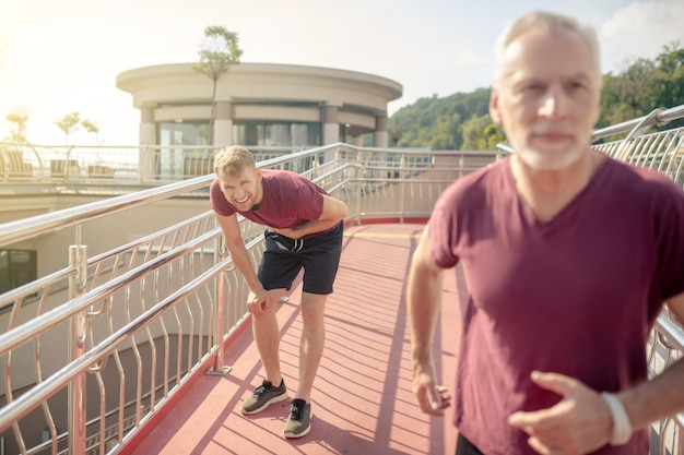 Grey-haired male running across bridge, young male holding hand on his chest behind him