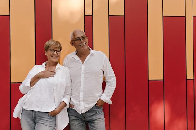 안경에 회색 머리 남자와 현대 셔츠 웃 고 붉은 색과 오렌지색에 가벼운 옷에 금발 머리를 가진 여자와 포즈.