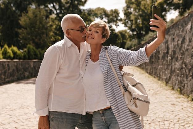 Седовласый мужчина в белой рубашке и джинсах фотографируется и целует свою жену с короткими волосами в полосатой блузке с рюкзаком в парке.