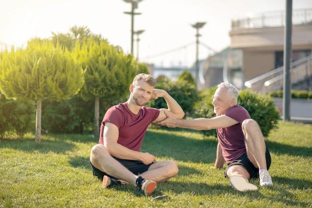 ひげを生やした男性の上腕二頭筋に触れる白髪の男