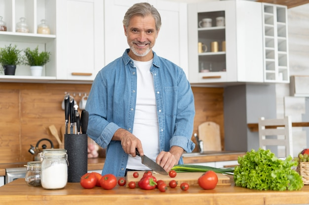 Седовласый зрелый красавец готовит вкусную и здоровую пищу на домашней кухне.