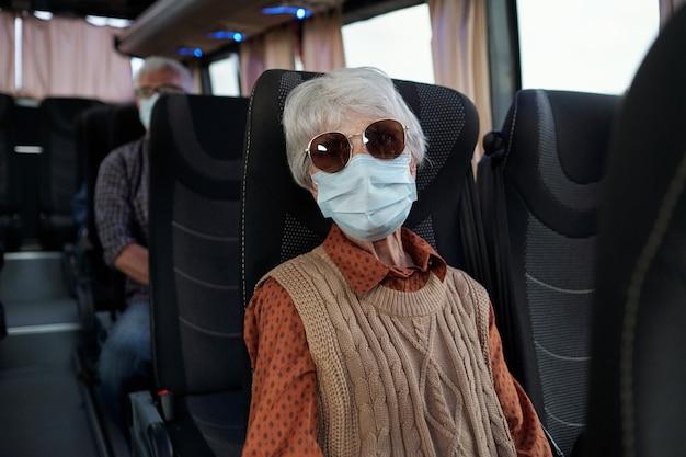 Седовласая зрелая женщина в защитной маске едет на автобусе