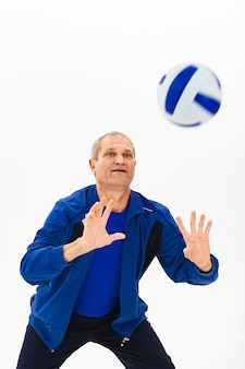 Grey-haired old athlete in blue tracksuit plays with ball on white
