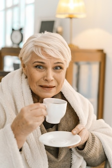 Grey-haired old woman drinking hot tea and relaxing at home