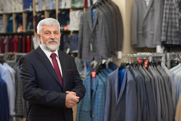 Grey haired owner of male boutique standing in it.