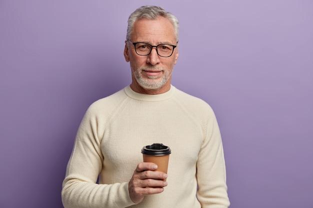 회색 머리 수석 남자는 투명한 안경과 흰색 스웨터를 입고 서서 뜨거운 음료를 식히고 즐거운 대화를 즐기고 자주색 배경에 포즈를 취합니다.