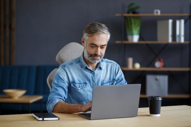 ノートパソコンを持ってホームオフィスで働く白髪の年配の男性。