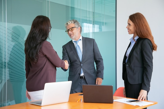 Grey-haired senior manager handshaking and greeting businesswoman