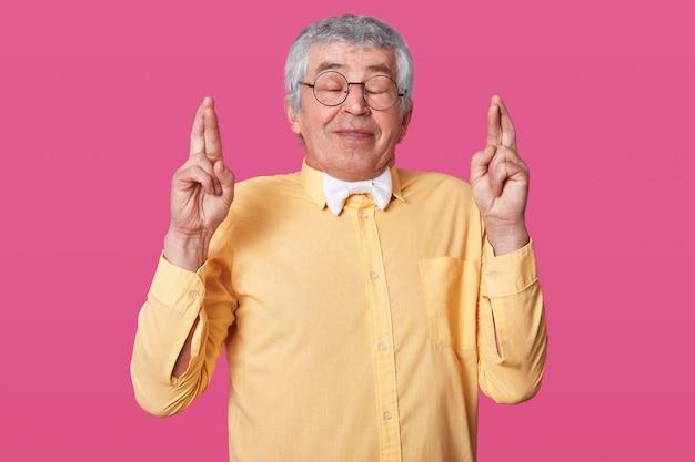 灰色の髪のシニアは手を挙げて指を交差させます。