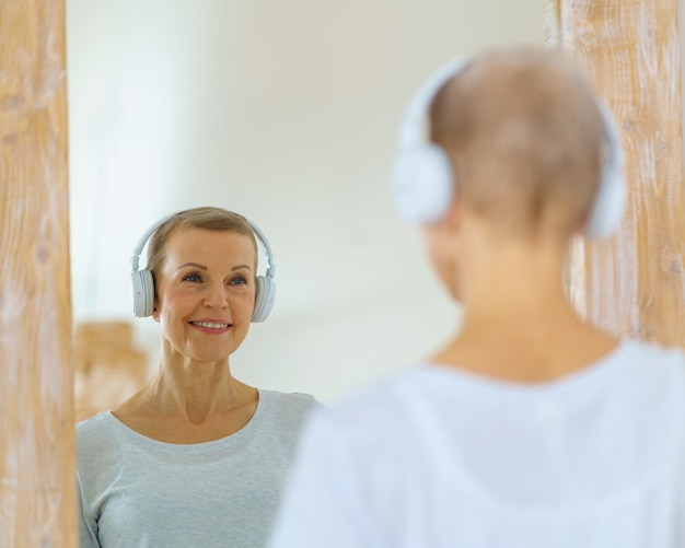 Grey haired senior woman with headphones on admiring herself in the mirror