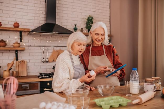 キッチンで料理が上手なエプロンの白髪の笑顔の女性