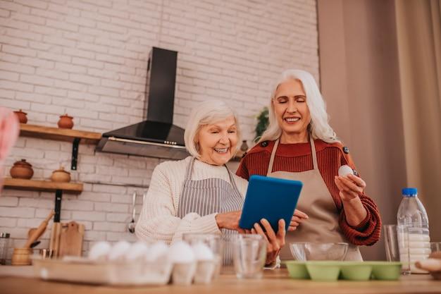 新しいレシピを読んでエプロンで白髪の笑顔の女性