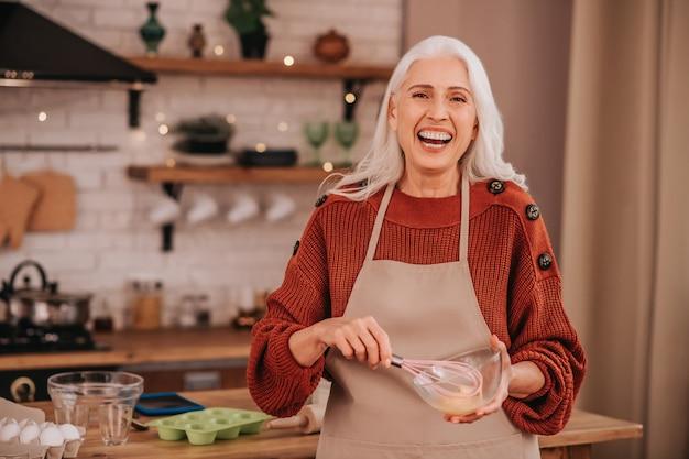 ボウルに明るいホイップミルクを笑顔灰色の髪の笑顔の女性