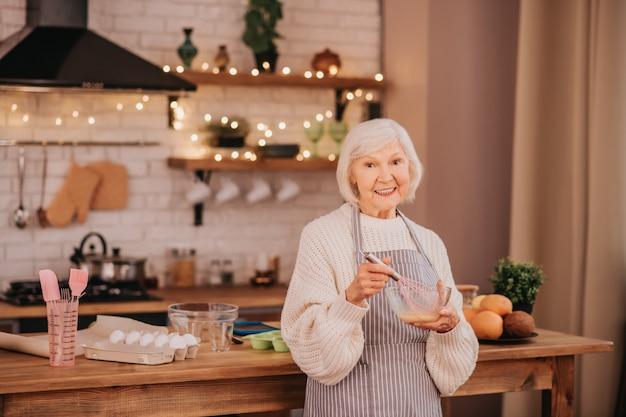 台所のテーブルの近くに立っている白髪の笑顔の女性