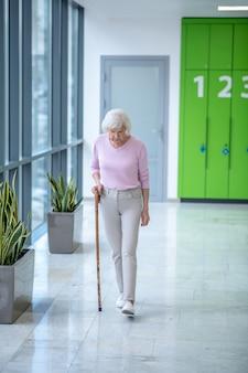 Седая женщина с тростью гуляет по коридору