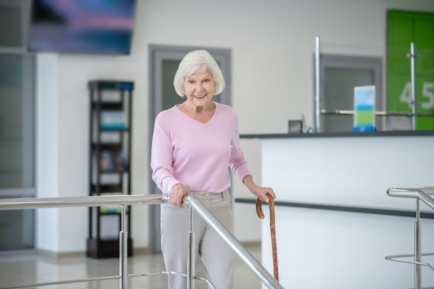 Grey-haired woman with a walking stick smiling