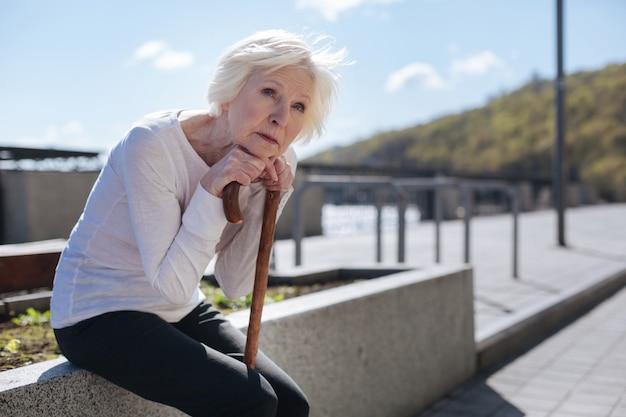 Седовласый добрый слабый пенсионер сидит на бетонной плите, смотрит в небо и запоминает этот момент