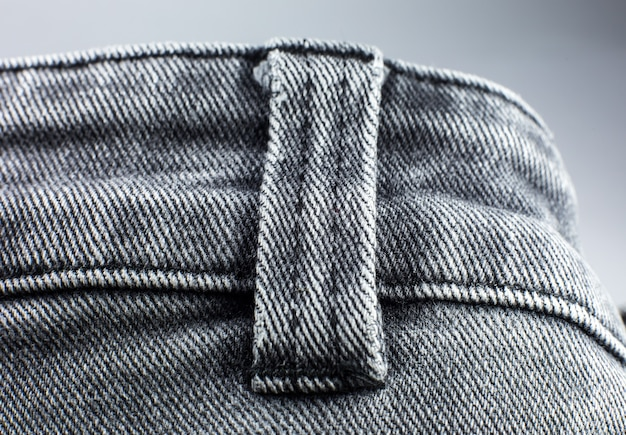グレーのヒップスタージーンズ素材。灰色の布のテクスチャの背景。