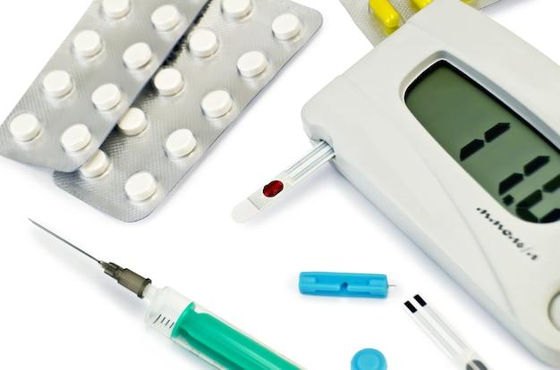 Серый прибор для измерения сахара в крови с тест-полоской, таблетками и капсулами в пачках