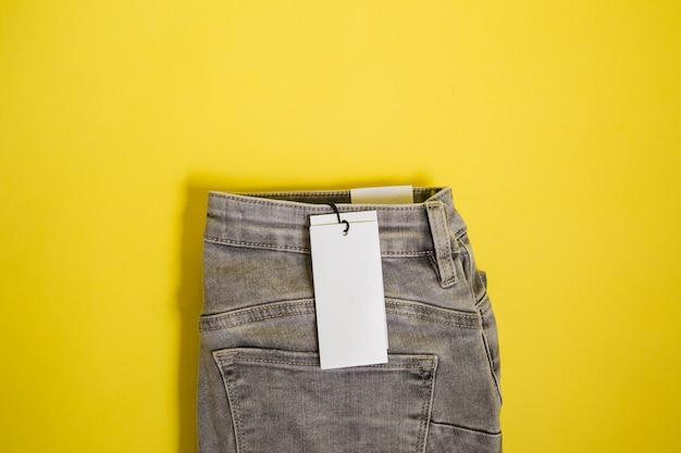 Серые джинсы с биркой на желтом фоне с пространством для текста