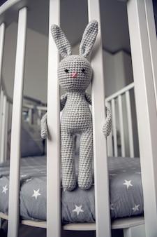 ベッドのパーティションの後ろに座っている灰色のニットウサギ