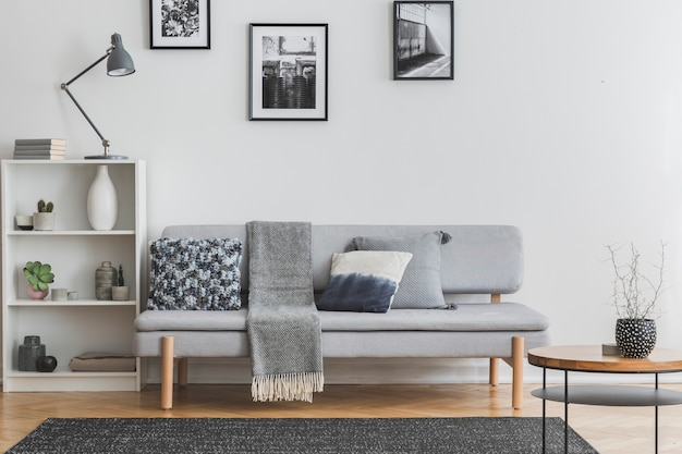 Grey lamp on white bookshelf with vases and books next to elegant settee